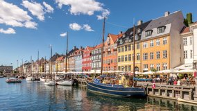 Nyhavn canal (New Harbour), a 17th-century waterfront and entertainment district in Copenhagen, Denmark. Colorful houses facades and sailing boats. White clouds move across blue sky. Time lapse video.