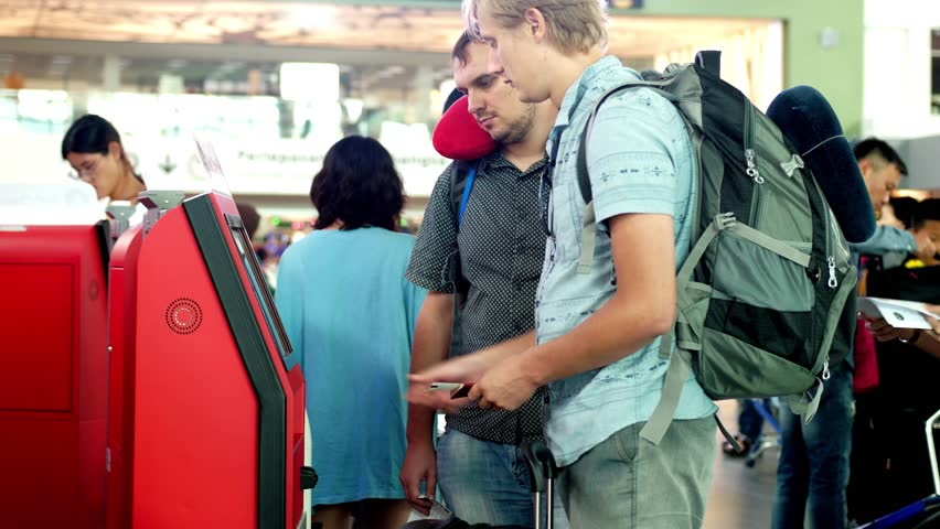 Singapore, 13 july 2018. Traveling men with backpacks check-in at selfthems help desk in the airport.  | Shutterstock HD Video #1019830891