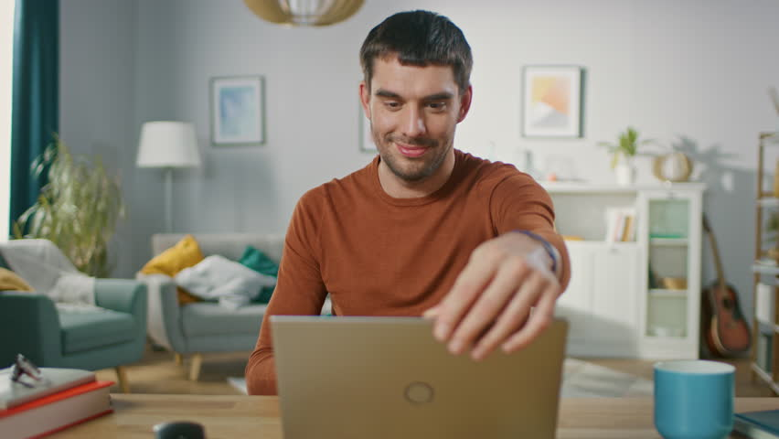 Confident Young Man Sitting at His Desk at Home, Opens and Starts Using Laptop. In the Background Living Room with Cozy Design.