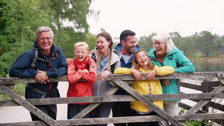 Multi generation family looking at camera standing behind wooden fence, Lake District, UK