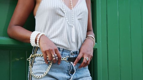 Trendy woman in striped camisole and side stripe jeans standing with thumbs in her belt, mid section