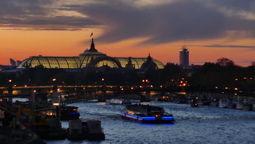 View on the Grand Palais (old monument in Paris). In the foreground there is the seine river and a boat. Filmed in the night.