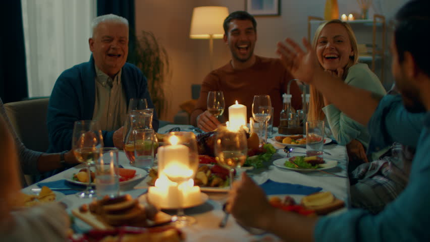 In the Evening: Family and Friends Gathered at the Dinner Table. Old and Young People Have Fun, Eating, Drinking. Applaud and Propose a Toast. Cozy Living Room Atmosphere.