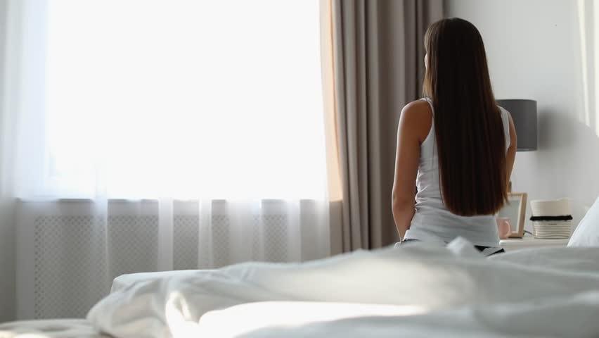 Young woman walking to window in bedroom. Beautiful lazy morning  | Shutterstock HD Video #1019852788