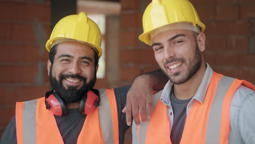 People working in construction site. Portrait of happy men at work in new house inside apartment building. Professional workers looking and smiling at camera as co-workers and friends. Slow motion