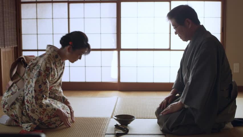 Authentic male tea master serving a bowl of hot matcha tea to a smiling geisha in a traditional Japanese room with soft day lighting. Medium shot on 4k RED camera on a gimbal.