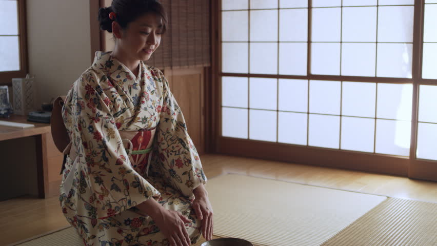 Happy female wearing kimono drinking a bowl of hot tea in a traditional Japanese room with soft day lighting. Medium shot on 4k RED camera on a gimbal.