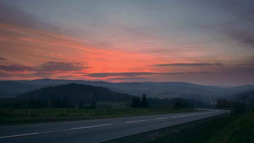 Car on the road between hills. Beautiful sunset with colorful sky. | Shutterstock HD Video #1019878348