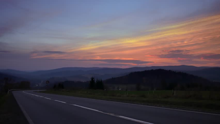 Car on the road between hills. Beautiful sunset with colorful sky. | Shutterstock HD Video #1019878351