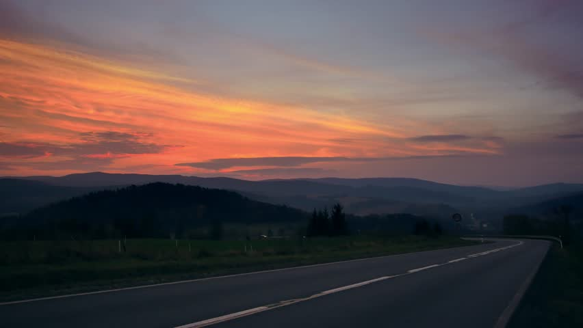 Car on the road between hills. Beautiful sunset with colorful sky. | Shutterstock HD Video #1019878354