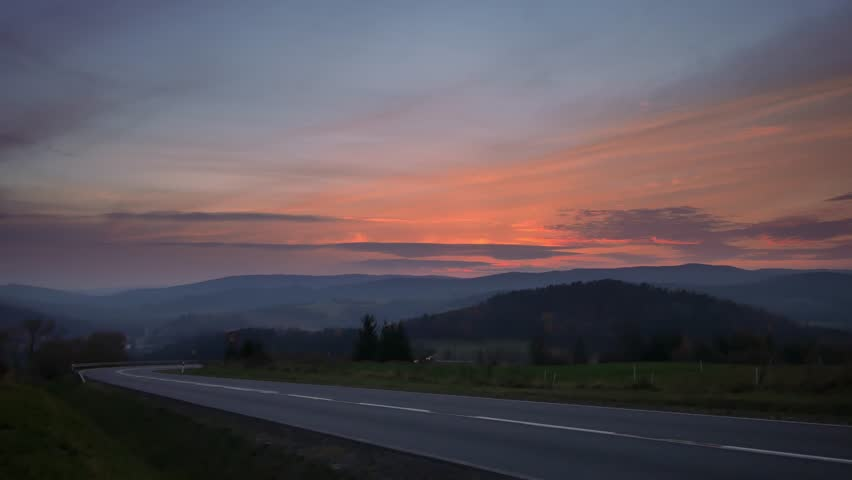 Car on the road between hills. Beautiful sunset with colorful sky. | Shutterstock HD Video #1019878357