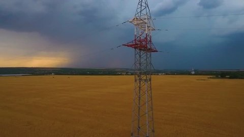 Huge storm cloud on the horizon bursts lightnings, power line pole on the wheat field up front