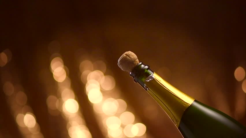 Champagne explosion. Sparkling wine popping, opening champagne bottle closeup. Sparkling Wine over Holiday Bokeh Blinking Background. Party, Success, holiday celebrating. Slow motion UHD 4K #1019898028