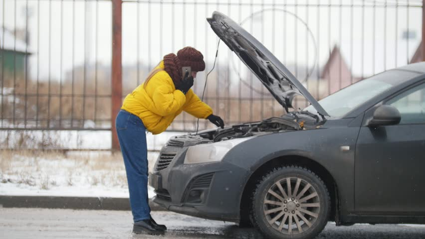 Car Trouble. Winter, cold weather. A young woman opens the hood, looking inside, rummaging in the engine, holding a phone | Shutterstock HD Video #1019901589