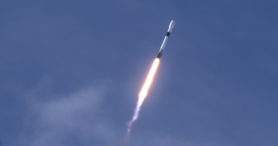 Rocket launching into space through blue skies and clouds. Flames and smoke trail behind the rocket. 4K video at 120 fps slow motion. With audio.