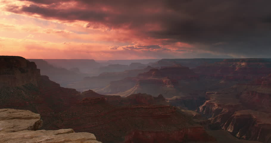 Amazing shot of Grand Canyon vista at sunset with beautiful lighting, clouds, red cliffs and blue skies in 4K DCI.