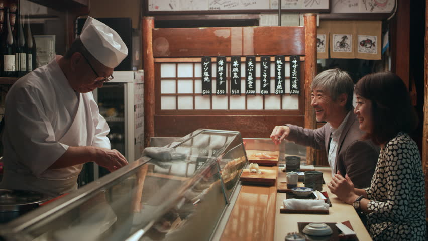 Smiling Japanese couple eating sushi and chatting with chef while he cooks in small sushi bar with soft interior lighting. Close up shot on 4k RED camera.