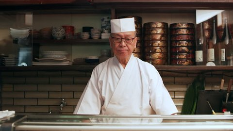 Portrait of experienced serious sushi chef standing behind a counter in his small traditional sushi bar with soft interior lighting. Medium shot on 4k RED camera.