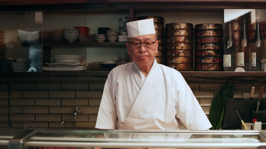 Portrait of veteran sushi chef with small smile standing behind a counter in his small traditional sushi bar with soft interior lighting. Medium shot on 4k RED camera.