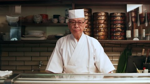 Portrait of Accomplished Japanese sushi chef standing behind a counter in his small traditional sushi bar with soft interior lighting. Medium shot on 4k RED camera.