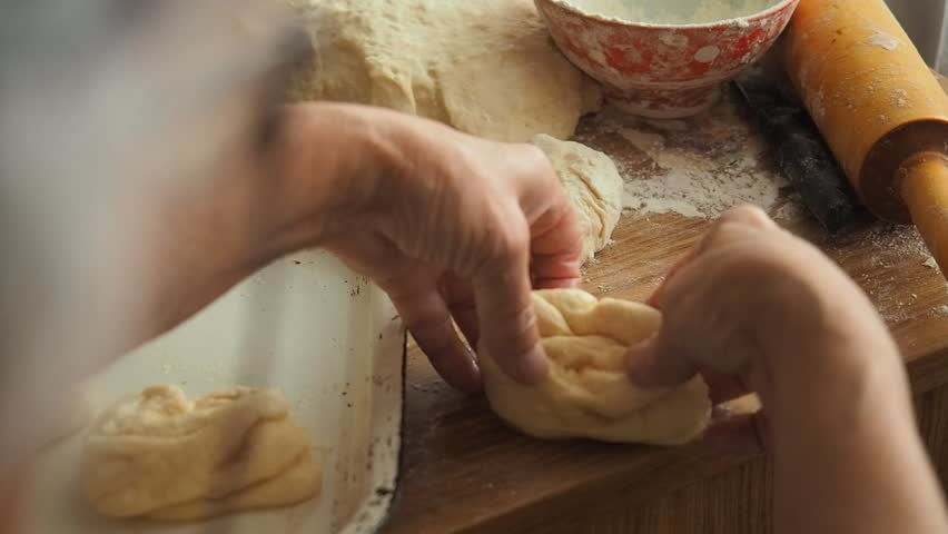 Grandmother cooking, preparing dough in flour, granny hands close up. Senior woman baking pastry in her home kitchen.