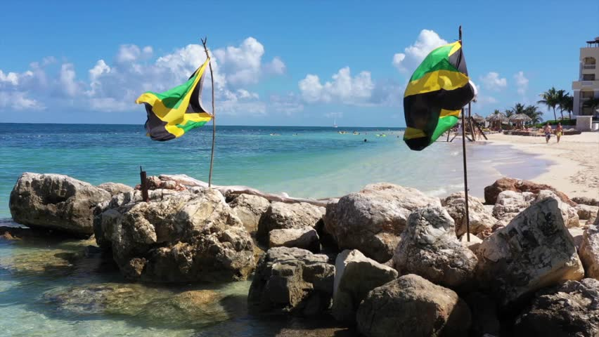 Aerial footage of jamaican flags on a beautiful tropical caribbean beach on Jamaica   Shutterstock HD Video #1019944492