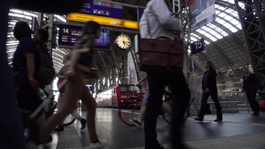 Commuters walk fast, people hurry run to train in Frankfurt Main Railway Station. Passengers go in rush inside Deutsche Bahn Central Building, Frankfurt Hauptbahnhof interior, Germany, April 20, 2018