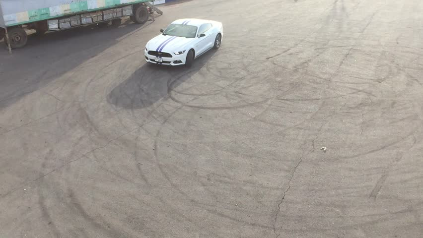 Yerevan, Armenia - 01 May 2017. Pearl white Ford Mustang GT making donuts with massive smoke and crazy V8 engine sound.