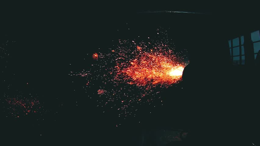 Air carbon arc cutting at the metal construction factory in a super slow motion. A lot of red-hot sparks flies around. Dangerous work at the metal workshop. Heavy industry and metalwork