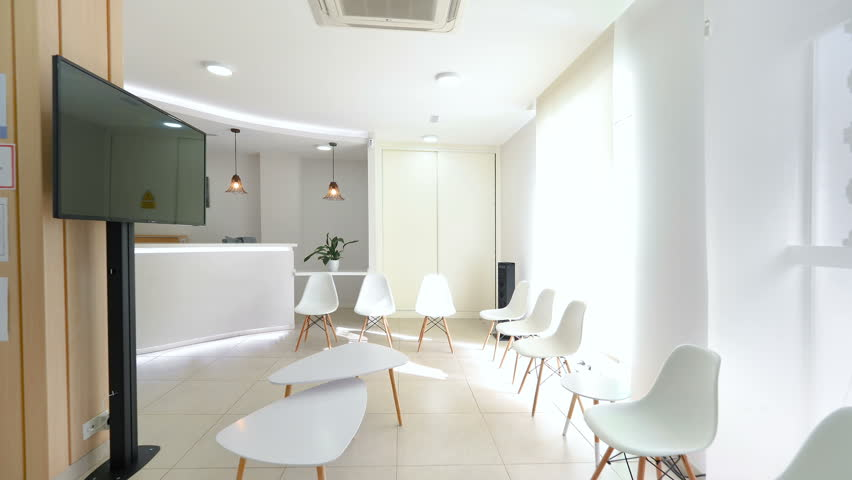 Panorama of a bright reception and waiting room in a clinic with desk, modern chairs and plants.