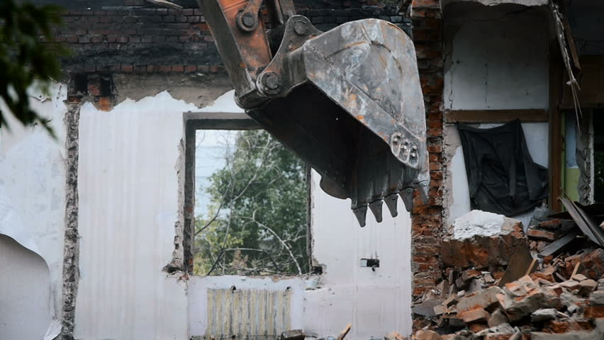 Backhoe excavate broken bricks and stones are falling down destroy the walls windows and ceiling near the old empty abandoned building busted and shattered building
