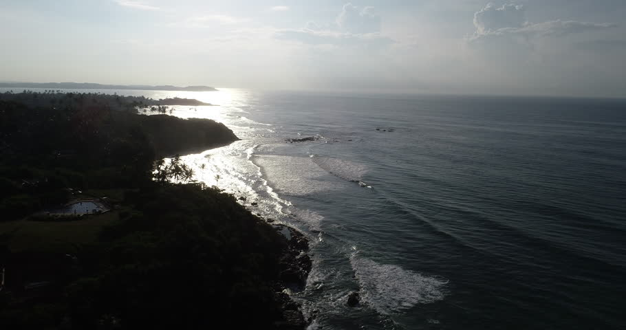 Aerial view.Drone ascent aerial footage of ocean waves and weligama cap in the sunrise landscape   Shutterstock HD Video #1019994136
