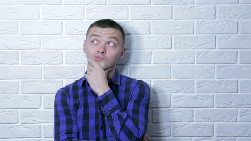 Young adult business man standing over white brick wall serious face thinking about question Royalty-Free Stock Footage #1019996995