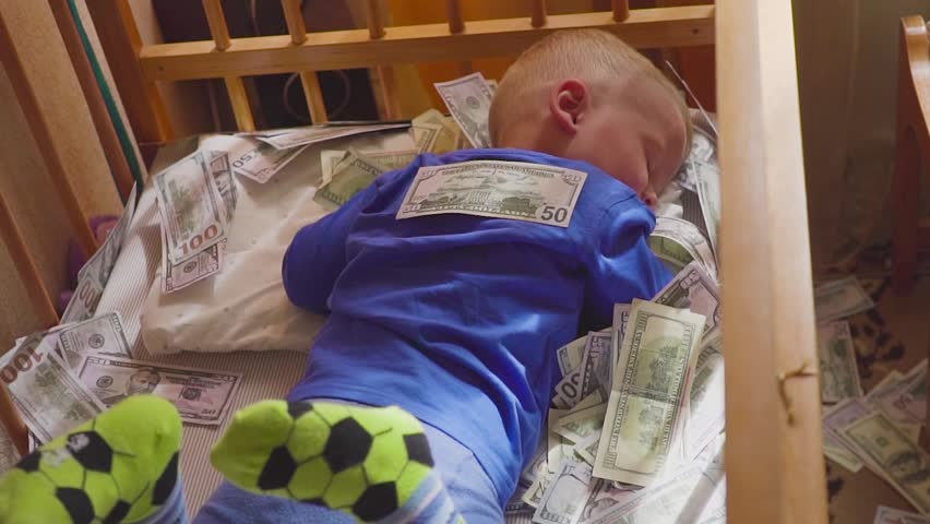 sleeping baby and falling money. Concept unexpected wealth. A big win.