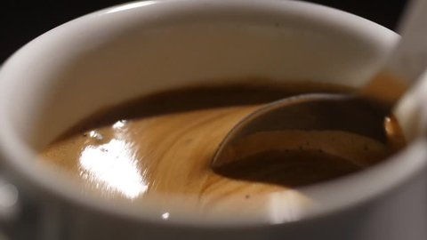 mixing espresso coffee with spoon after putting sugar slow motion