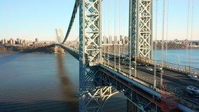 Aerial drone footage of George Washington Bridge with view along Hudson River, towards New York City (upward movement)