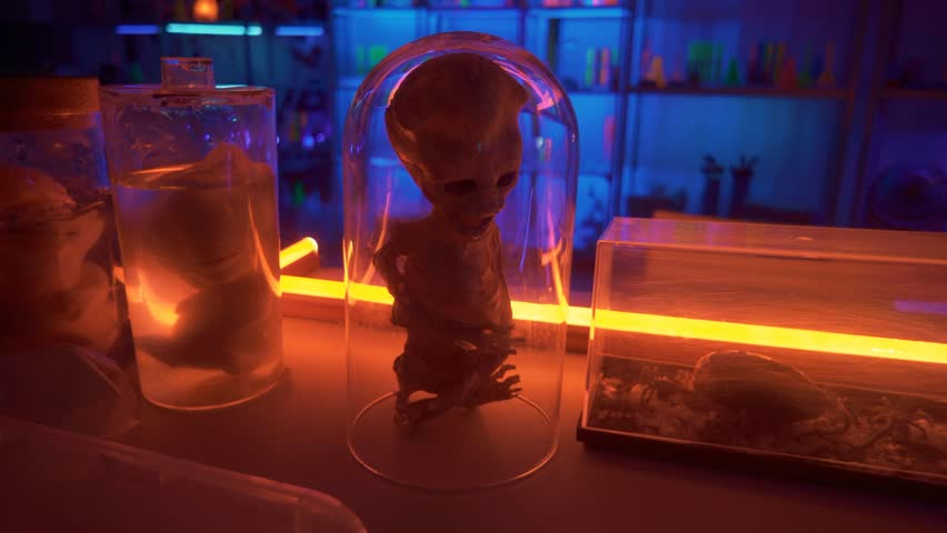 Alien mummy on table red lights creatures tubes. Red and blue light illuminate the room.On table are containers with other UFO creatures