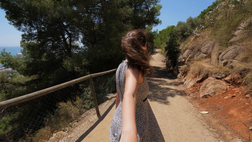 Woman walk in forest near blue sea, hold hand following man, Barcelona, Spain. Follow me concept | Shutterstock HD Video #1020079471