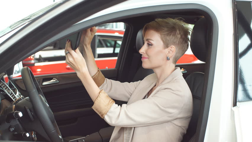 Customer female loving her new car. Excited young blonde woman admires her red glistening new car at the car dealership. Successful businesswoman buying vehicle transport with insurance.