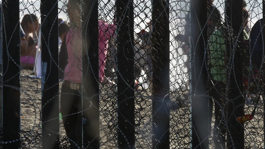 San Diego, California, U.S.A November 2018.  Two males of the Central American migrant caravan look through the Mexico/United States border wall from the Mexico side at Tijuana Beach.