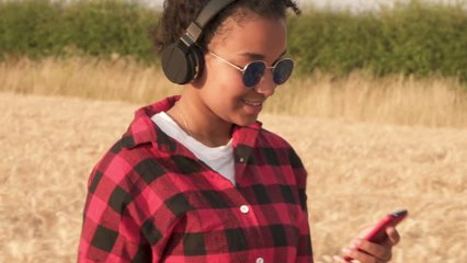 Slow motion tracking video clip of beautiful mixed race African American girl teenager young woman wearing a red and black shirt and blue sunglasses walking listening to music on wireless headphones