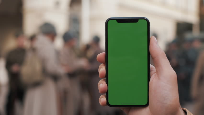 Closeup of a man's hand holding and using mobile telephone with a vertical green screen on the streets. Military soldiers in the background | Shutterstock HD Video #1020111583