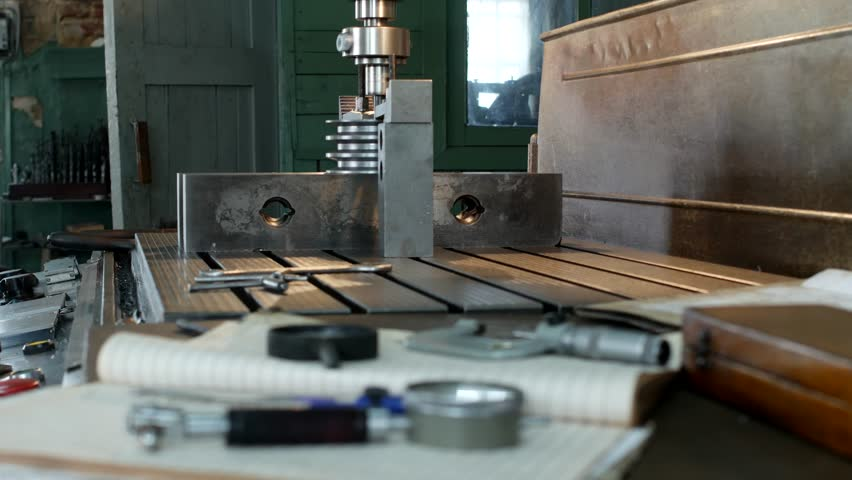 A private workshop for working with metal parts, in the background a drilling machine drills a hole in the pulley, on the table lie measuring tools, production, small business | Shutterstock HD Video #1020123439