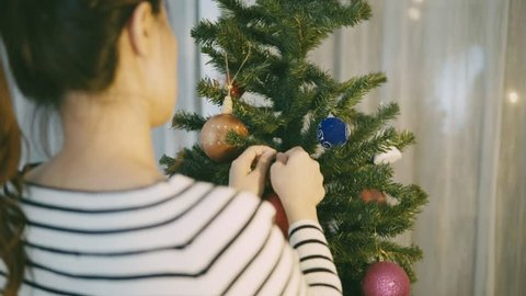 Girl hands decorate christmas tree