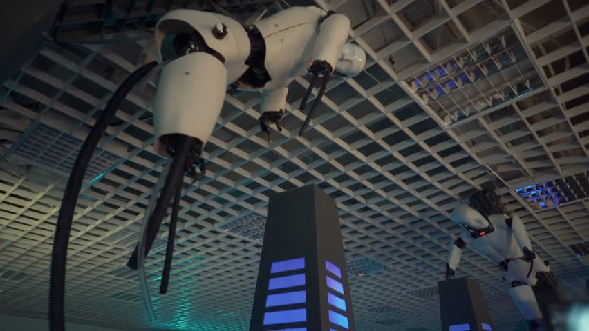 Toliatty, Samarkaya obl. / Russia - 11 24 2018: Two robots without legs fixed on the ceiling. Both robots rotate their heads from side to side. Nearby is a glowing blue pillar.