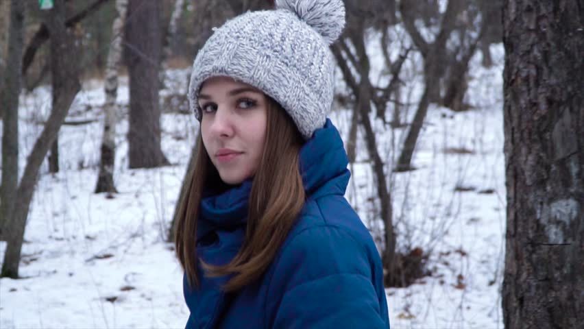 Young woman walking in winter. Attractive woman in winter hat walking in park among trees and snow. Beautiful woman sadly thoughtful looking at his feet walking alone | Shutterstock HD Video #1020140605