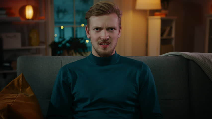 Portrait of a Handsome Man Sitting on a Couch at Home at Night, Watching Gore Horror Movie on TV. He Gets Really Scared and Disgusted. | Shutterstock HD Video #1020144148