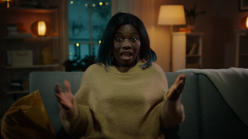 Portrait of a Young Black Girl Sitting on a Couch at Home at Night, Watching Horror Movie on TV. She Gets Really Scared and Emotional. | Shutterstock HD Video #1020144442