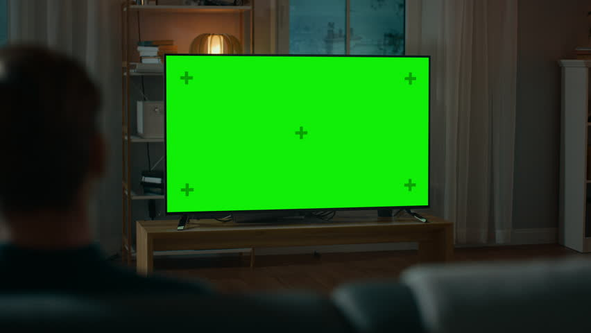 Man Watches Green Mock-up Screen TV while Sitting on a Couch at Home in the Evening. Cozy Living Room with Warm Lights. Over the Shoulder Shot. | Shutterstock HD Video #1020144451