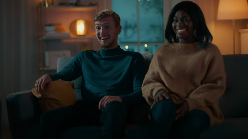 Happy Diverse Young Couple Watching Comedy on TV while Sitting on a Couch, they Laugh and Enjoy Show. Handsome Caucasian Boy and Black Girl in Love Spending Time Together. Moving Camera Shot. | Shutterstock HD Video #1020145084